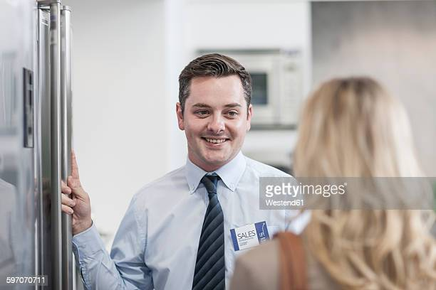 shop assistant smiling at customer - electronics store stock photos and pictures