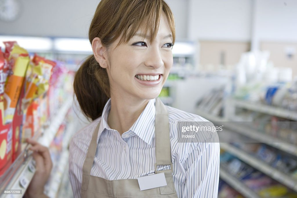Shop assistant smiling in store, looking away : Stock Photo