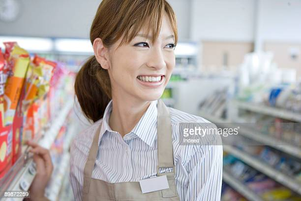 Shop assistant smiling in store, looking away