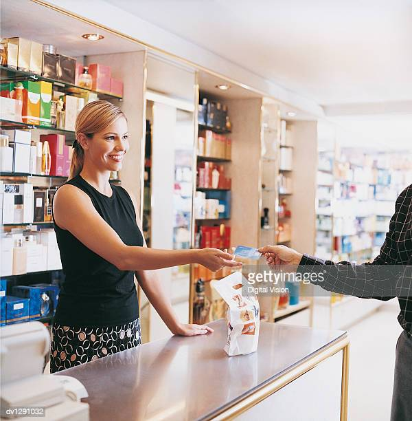 Shop Assistant Standing By the Checkout Counter in a Drugstore Being Handed a Bank Card By a Customer