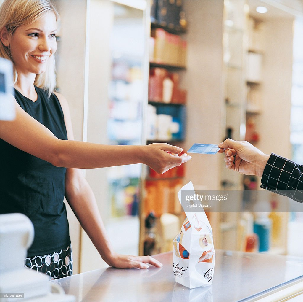 Shop Assistant Standing By the Checkout Counter in a Drugstore Being Handed a Bank Card By a Customer : ストックフォト