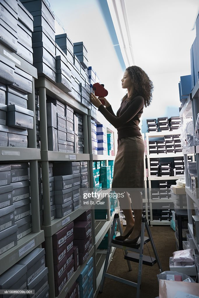 Shop assistant standing on step ladder labeling shoe boxes in storage room, side view : Stockfoto