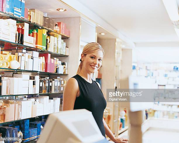 Shop Assistant Stands Behind Perfume Counter Smiling at Camera
