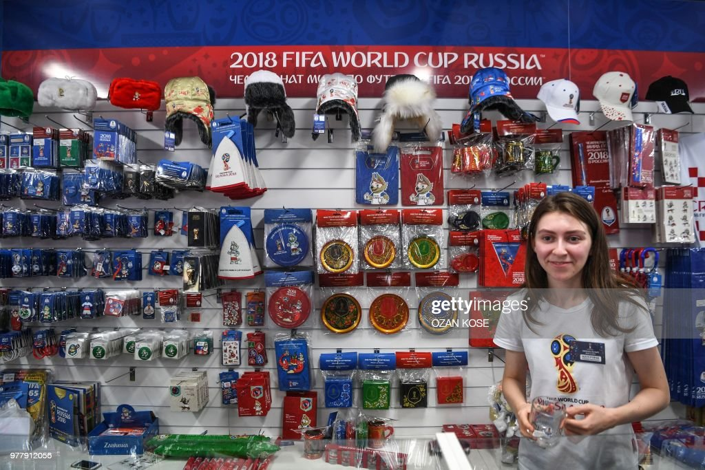 A Shop Assistant Stands In An Official Fifa Football Fan Shop In