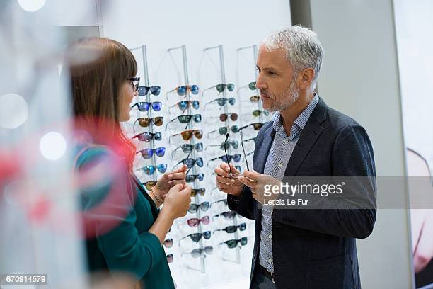 Shop assistant talking with customer in optical shop
