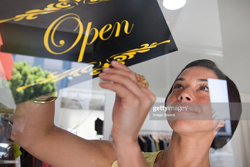 Shop assistant turning sign in shop window : Stock Photo