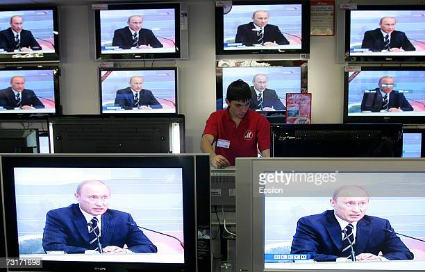 A shop assistant watches TV screens in a shop during the broadcasting of Russian President Vladimir Putin's annual address to Russian and foreign...