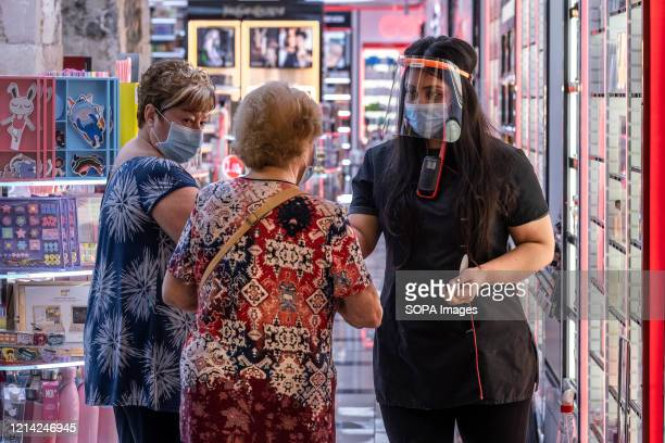 Shop assistant wearing a face shield as a preventive measure attends to two clients inside a perfumery. The small and medium-sized retail business in...