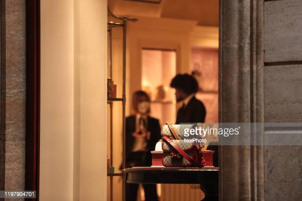 Shop assistant wearing a protective respiratory mask inside a luxury showroom in downtown Rome on February 1, 2020