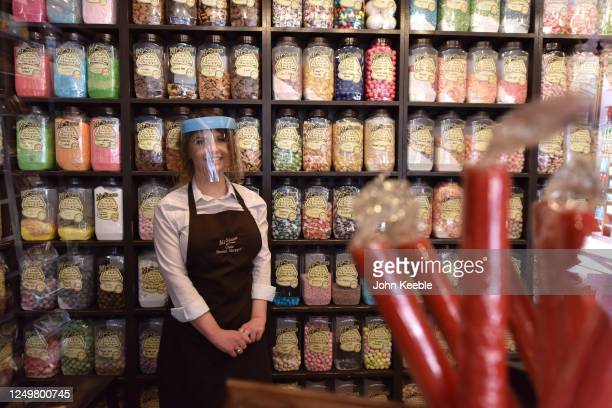 Shop assistant wearing gloves and face shield poses in the Mr Simms Olde Sweet Shoppe on June 15, 2020 in Southend on Sea, United Kingdom. The...