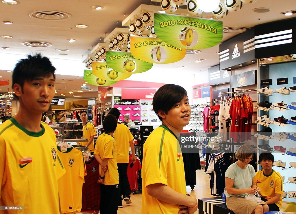 Shop assistants in Brazilian jerseys stand next to World Cup 2010 accessories and decorations while waiting for customers in Hong Kong on June 5, 2010. The World Cup football 2010 starts on June 11.