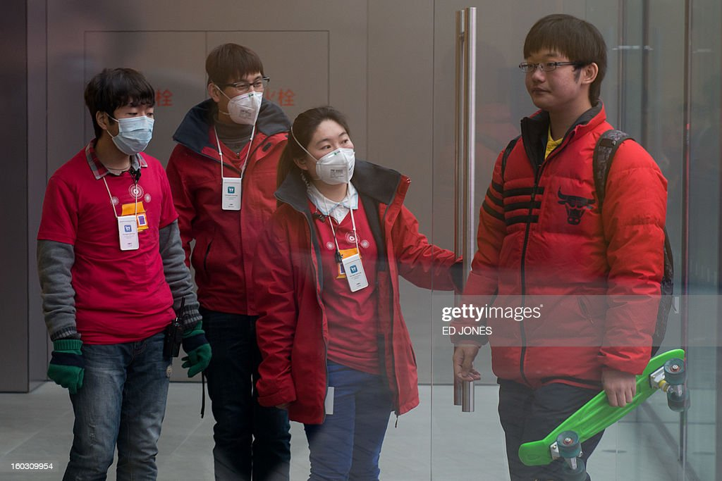 Shop assistants welcome customers during a spell of heavy pollution in Beijing on January 29, 2013. Pollution levels in Beijing rose above index limits, the US embassy said, as a dense cloud of haze shrouded large swathes of northern China. AFP PHOTO / Ed Jones