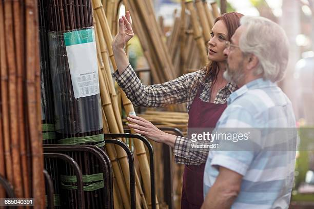 Shop assistent and client in garden centre looking at bamboo fencing