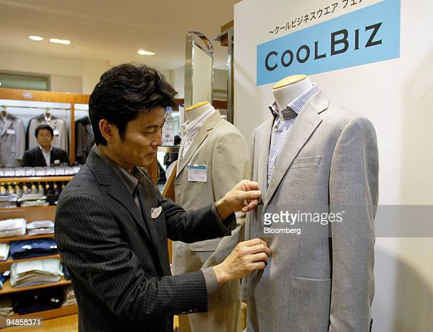 """Shop attendant adjusts a suit at a """"Cool Biz"""" clothing display in a Mitsukoshi department store in downtown Tokyo Friday, July 1, 2005."""
