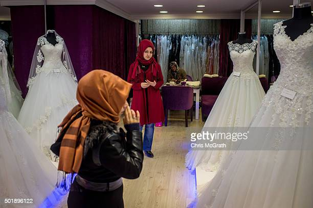 A shop attendant watches on as a woman tries to decide on a wedding dress at a store in the Fatih district on December 18 2015 in Istanbul Turkey...