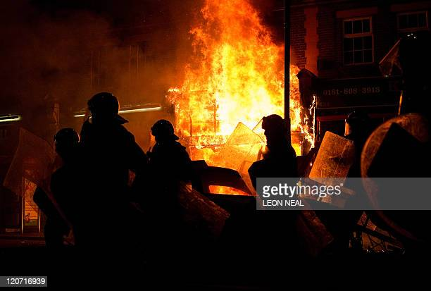 A shop burns as riot police try to contain a large group of people on a main road in Tottenham north London on August 6 2011 Two police cars were on...
