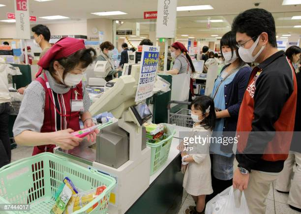 Shop clerks wearing facemasks work at checkout counters at a market in Osaka in western Japan on May 17 2009 Japan said May 17 that 20 more people...