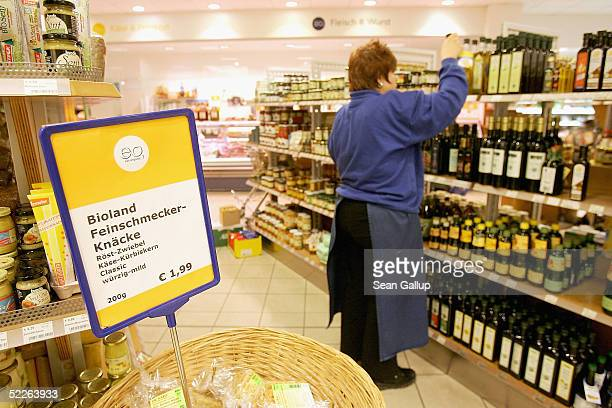 A shop employee adds bottles of oil to a shelf at a store of German organic supermarket chain EO Komma March 2 2005 in Berlin Germany According to...