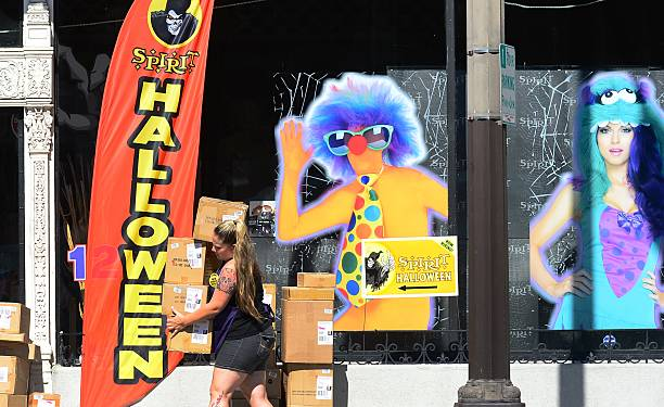a shop employee carries boxes of items for sale ahead of halloween on october 16