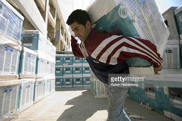 A shop employee moves an imported Iranian cooler to a truck in the Karrada neighborhood on March 4 2007 in Baghdad Iraq Since the US invasion in 2003...