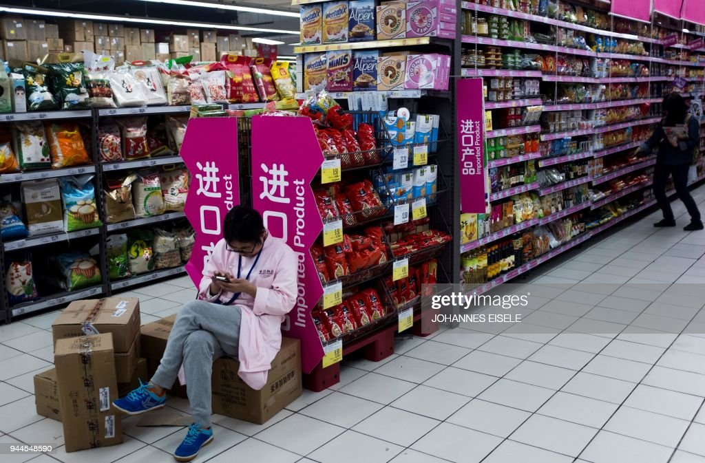 A shop employee sits next to a shelf of imported foods at a