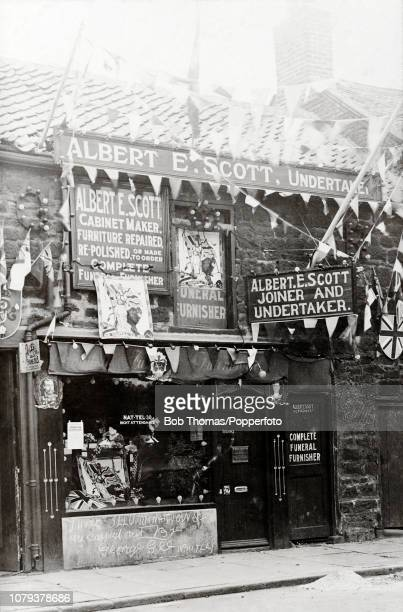 Shop front of Albert Ernest Scott, undertaker, joiner, cabinet maker, and general furnisher, including a notice about coronation celebrations and...