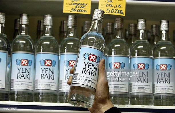 Shop keeper shows a legally produced Turkish Raki in Istanbul 03 March 2005. The deaths of nine people from bootleg liquor has sparked panic in...