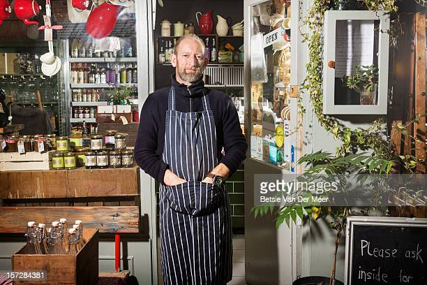 shop keeper standing in front of shop. - self sufficiency stock pictures, royalty-free photos & images