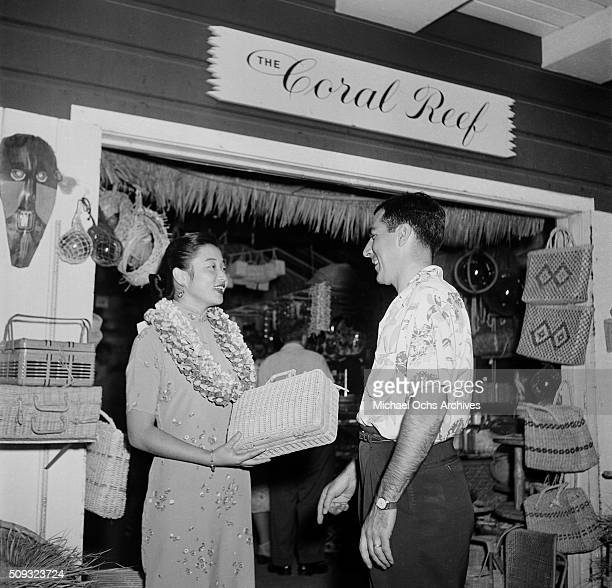A shop keeper waits on a customer at the Coral Reef shop at the farmers market in Los AngelesCalifornia