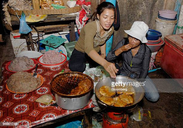 Shop keepers cook street food at their stall in the old market of Siem Reap Cambodia on Tuesday Nov 27 2007 Cambodia's economy will probably expand...