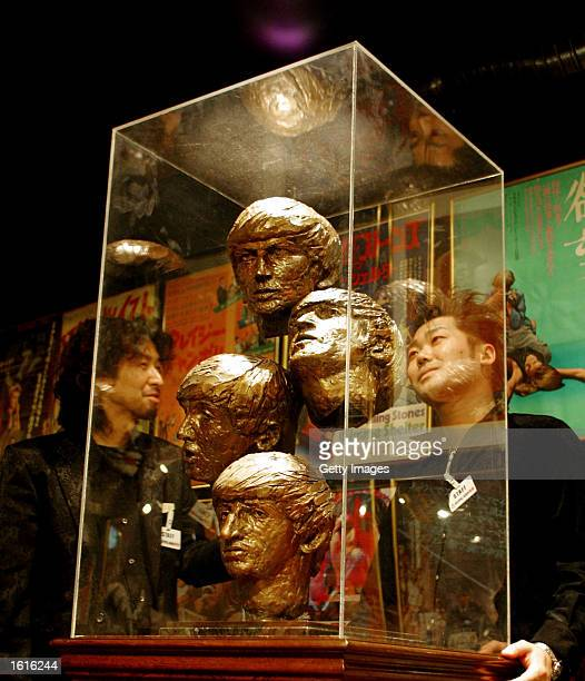 Shop keepers talk around a statute Beatles Four Heads created by a British sculptor David Wynne in1964 Paris at the Rock'n Roll Museum November 12...