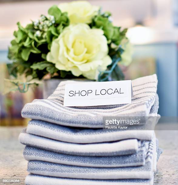 shop local sign on stack of pretty tea towels - gift shop stock pictures, royalty-free photos & images