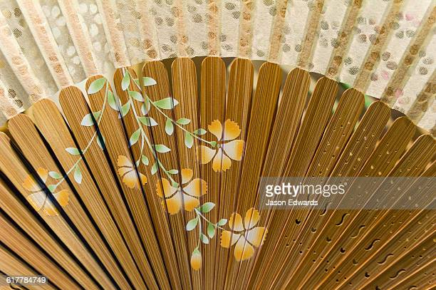 A shop near a temple sells delicate traditionally decorated Japanese fans.