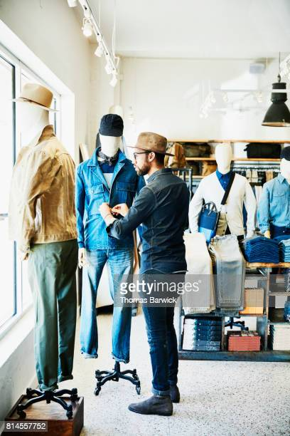 Shop owner adjusting clothes on manikin in mens clothing boutique