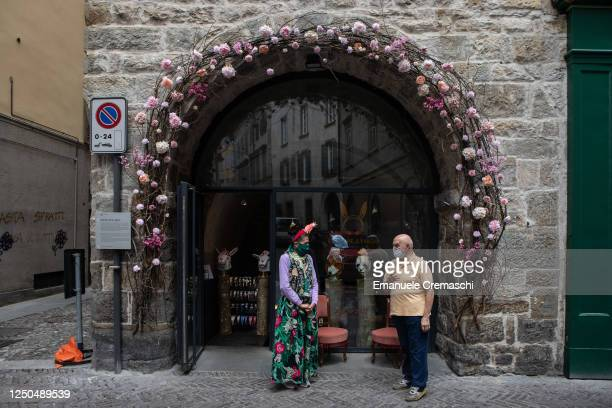 Shop owner and a friend talk to each other in the streets of the Upper Town while wearing face masks on June 18, 2020 in Bergamo, Italy. The city of...