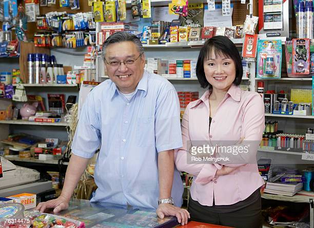 shop owner and wife, behind shop counter, portrait - convenience store stock photos and pictures