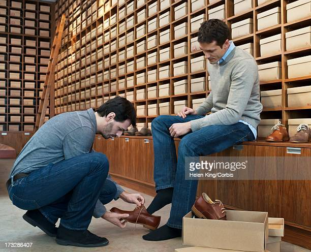 shop owner attending customer in shoe store - shoe store stock pictures, royalty-free photos & images