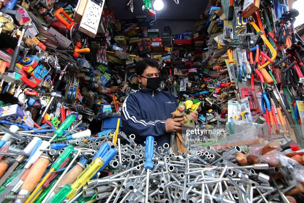 A shop owner cleaning hardware items in Srinagar, Kashmir on June 13,...  News Photo - Getty Images