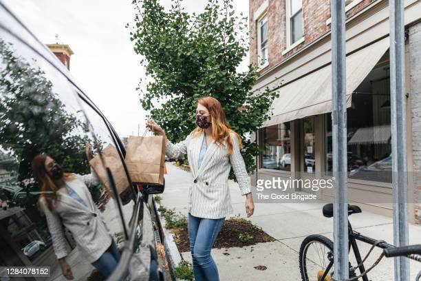 shop owner delivering purchase to customer in car - curbside pickup stock pictures, royalty-free photos & images