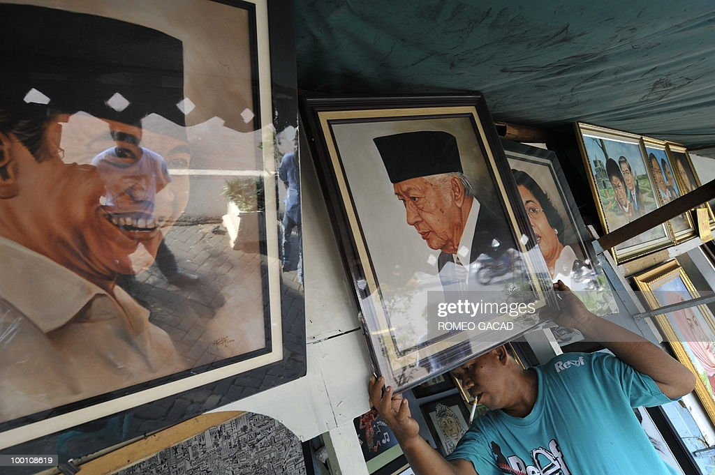 A shop owner displays painting portraits of Indonesian military strongman Suharto and former president Megawati Sukarnoputri at a pavement gallery in Jakarta on May 21, 2010. Twelve years after the dawning of Indonesia's 'Reformasi' movement with the Suharto's resignation there are fears the country of 240 million people is on a slipperly slope backwards.