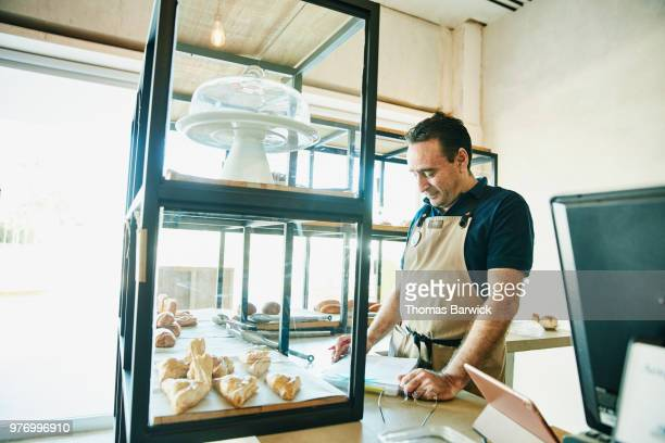 Shop owner doing paperwork behind counter in bakery