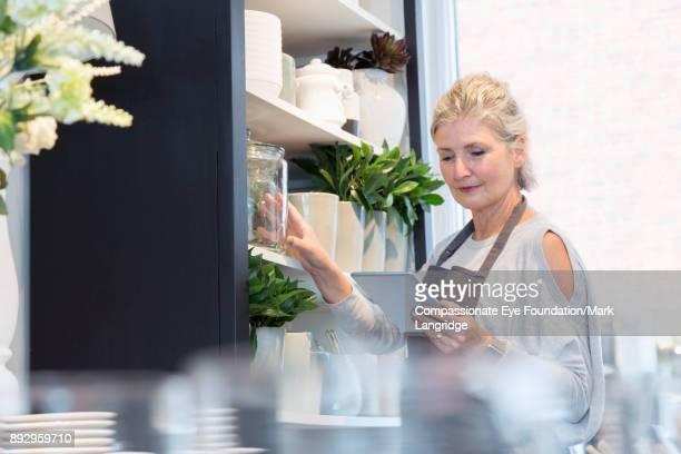 Shop owner doing stock check with digital tablet