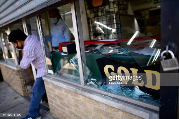 A shop owner exits his damaged store in the aftermath of widespread unrest following the death of George Floyd on June 1 2020 in Philadelphia...