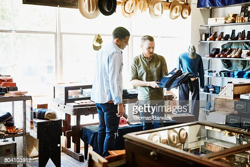 Shop owner explaining difference in denim jeans to customer in store