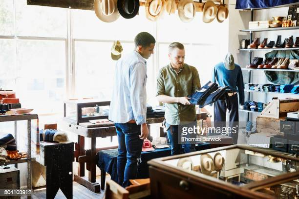 shop owner explaining difference in denim jeans to customer in store - only young men stock pictures, royalty-free photos & images