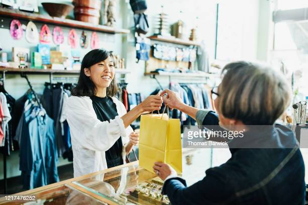 shop owner handing bag to smiling client after shopping in clothing boutique - giving stock pictures, royalty-free photos & images