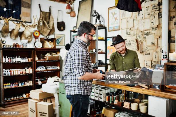 Shop owner helping customer check out in mens boutique