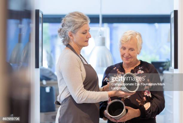 shop owner helping customer choose ceramic pot - craft product stock pictures, royalty-free photos & images