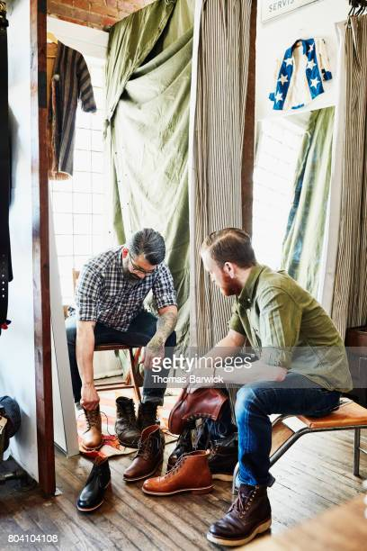 Shop owner helping customer try on boots in mens boutique