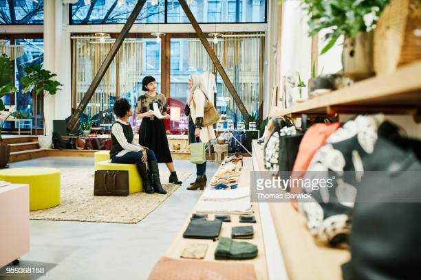 shop owner helping friends decide on shoes while shopping in boutique - older women in short skirts stock pictures, royalty-free photos & images